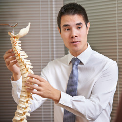 A photo of a man holding a spine.